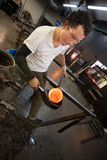 Man Working with Hot Glass. Small business glass manufacturer forming glowing hot object Royalty Free Stock Image
