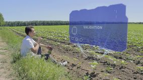 Man is working on HUD holographic display with text Validation on the edge of the field. Businessman analyzes the situation on his plantation. Scientist stock footage