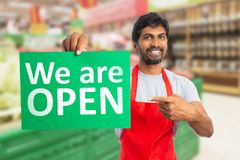 Man working at hypermarket pointing at we are open paper stock photography