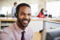 Free Man Working In A Call Centre Smiling To Camera, Close-up Royalty Free Stock Photography - 127008687