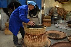 ANHUI PROVINCE, CHINA – CIRCA OCTOBER 2017: A man working inside a tea factory. A man working inside a tea factory with the big wicker basket, where si stock photography