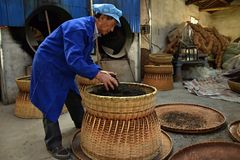 ANHUI PROVINCE, CHINA – CIRCA OCTOBER 2017: Men working inside a tea factory. A man working inside a tea factory with the big wicker baskets, where si the royalty free stock image