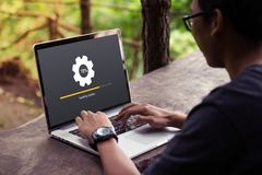 Man working and Installing update process with gearbox percentage progress and loading bar on laptop / computer. At the park / outdoor royalty free stock photos