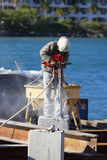 Man working with jackhammer. In a harbor Stock Images