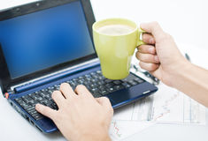 Man working on laptop. With a cup of coffee in his hand, some graphics underneath the laptop Royalty Free Stock Photo