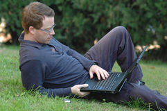 Man Working on Laptop. Out side in the park Stock Image