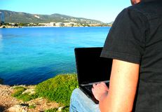 Man working on a laptop. Man and laptop by the sea Royalty Free Stock Photos