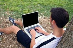 Man working on Laptop. Man sitting in a park working on his laptop computer Royalty Free Stock Image
