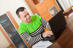 Man working on laptop. Adult man sitting at his laptop at home stock photography