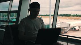 The man is working on laptop in the airport terminal stock video footage
