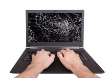 Man working on a laptop with a broken screen Stock Images