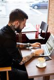 Man working with laptop in a cafe. Male with tatoos and beard sitting at the table and working with laptop Stock Photos