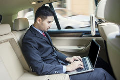 Man working with laptop in the car. Image of young businessman working with laptop computer inside the car Royalty Free Stock Photo