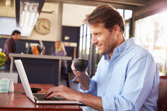 Man working on laptop in a coffee shop Royalty Free Stock Image