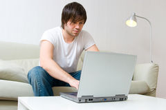 Man working on laptop computer. Young man sitting on sofa at home and working on laptop computer Royalty Free Stock Image