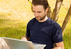 Man working on laptop computer outdoor in a park. Happy smiling forty years old caucasian man working on laptop computer outdoor in a park while sitting by a Royalty Free Stock Photos