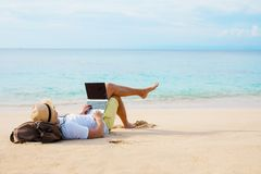 Man working on laptop computer. While relaxing on the beach Royalty Free Stock Photo