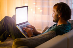 Man working on laptop in cozy home interior Royalty Free Stock Images