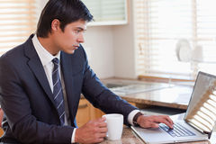 Man working with a laptop while drinking coffee Royalty Free Stock Images