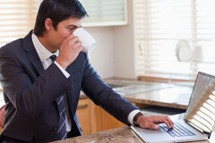 Man working with a laptop while drinking tea Royalty Free Stock Image