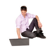 Man working on laptop of floor. Royalty Free Stock Images