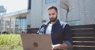 Man working on laptop. Handsome arab bearded man casual dressed working on laptop sitting before business center outdoors stock video