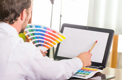 Man working on laptop while holding up pantone Stock Images