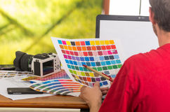Man working on laptop while holding up pantone Stock Image