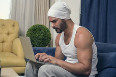 Man working on laptop at home, Handsome guy working on his noteb Royalty Free Stock Images