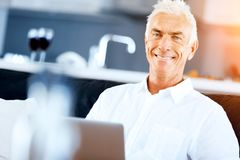 Man working on laptop at home. Senior handsome man in casual clothes working on laptop at home stock photography