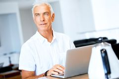 Man working on laptop at home. Senior handsome man in casual clothes working on laptop at home stock photo