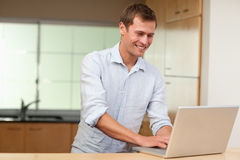 Man working on laptop in the kitchen Royalty Free Stock Images