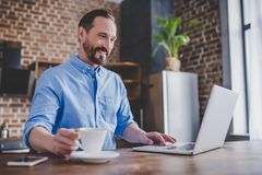 Man working on laptop at the kitchen. Man working on laptop and drinking coffee at the kitchen in the morning Stock Image