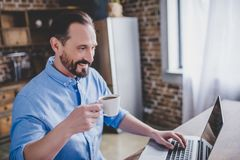 Man working on laptop at the kitchen. Portrait of smiling bearded man working on laptop and drinking coffee at the kitchen in the morning Royalty Free Stock Image