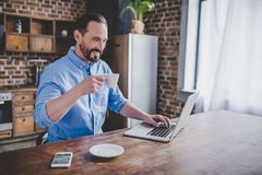 Man working on laptop at the kitchen. Portrait of smiling bearded man working on laptop and drinking coffee at the kitchen in the morning Royalty Free Stock Photography