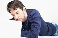 Man working on laptop while laying on the floor Stock Photos