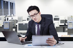 Man working on laptop while looking at tablet Royalty Free Stock Photos