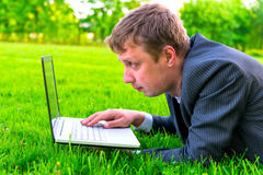 Man working with a laptop lying Royalty Free Stock Images