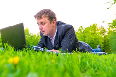 Man working with laptop lying. On the lawn Stock Images