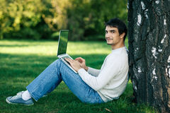 Man working with laptop outdoors. Smiling young man sitting near the tree stem and using laptop outdoors, looking at camera Stock Photography