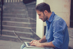 Man working on laptop outdoors sitting on steps outside of his office. Young man working on laptop outdoors sitting on steps outside of his office Royalty Free Stock Image