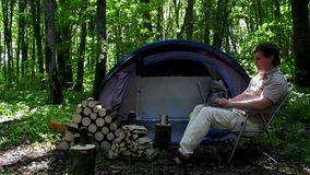 Man Working Outdoors In A Tent Camp. stock footage