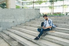 Man working on laptop outdoors. University student resting on campus and working on laptop Royalty Free Stock Photos