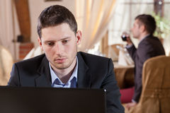 Man working on laptop in restaurant royalty free stock photo