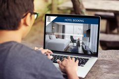 Man working on laptop, searching for lodging using on-line web service, booking a hotel on website stock image