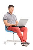 Man working on a laptop seated on a chair Royalty Free Stock Image