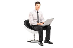 Man working on laptop seated in a modern chair Royalty Free Stock Images