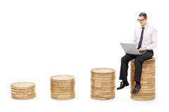 Man working on laptop seated on a stack of coins Stock Photo