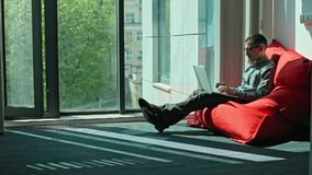 Man Working on Laptop and Sit in Bag Sacco. Man Working on Laptop and Sit in red Bag Sacco in coworking office stock footage