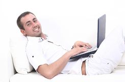 Man working on laptop, sitting on the couch Royalty Free Stock Photography
